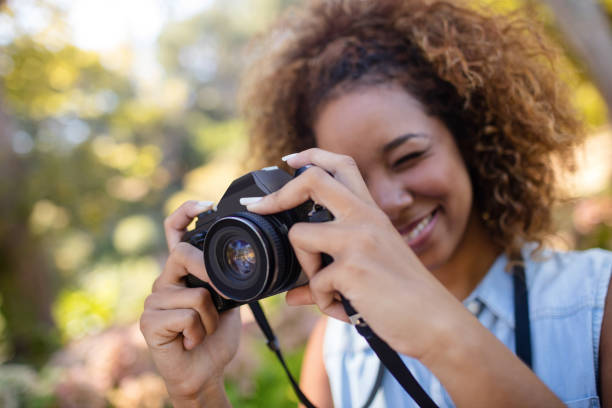 Woman taking picture with digital camera stock photo