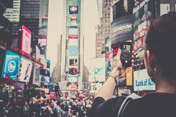frau nehmen bild mit handy am times square, nyc - new york new year stock-fotos und bilder