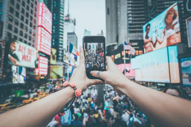 pov frau aufnahme mit handy bei times squares, nyc - sightseeing in new york stock-fotos und bilder