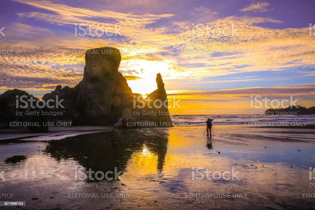 A woman taking pictures at bandon beach, Oregon stock photo