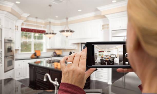Frau, die Bilder von einer benutzerdefinierten Küche mit ihrem Smartphone – Foto