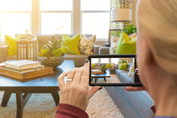woman taking pictures of a living room in model home with her smart phone - vendere foto e immagini stock