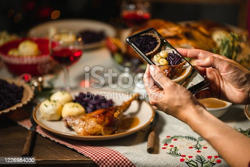 Female photographing a typical German Christmas dinner with her mobile phone. Female taking pictures of Christmas meal on table.
