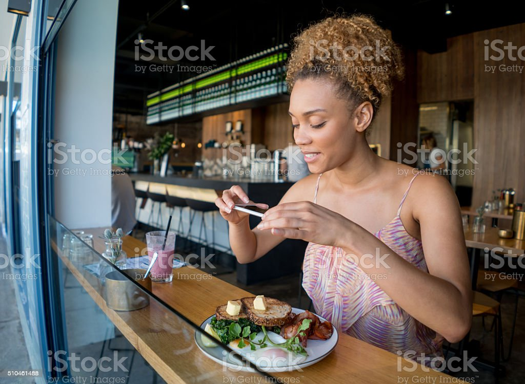 Woman taking pictures of food at a restaurant stock photo