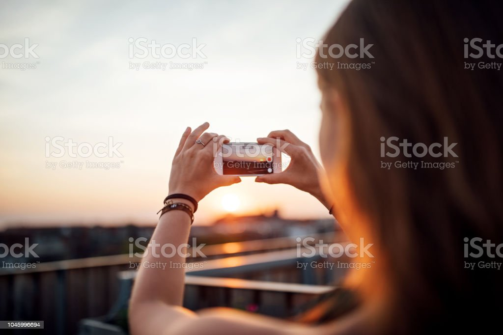 Woman taking pictures of sunset from rooftop stock photo