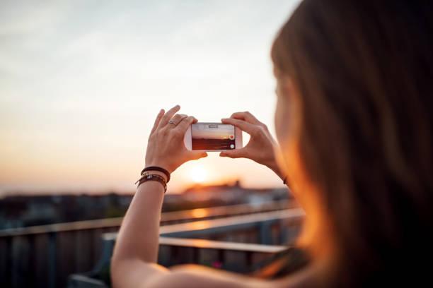 Frau, die die Bilder des Sonnenuntergangs vom Dach – Foto