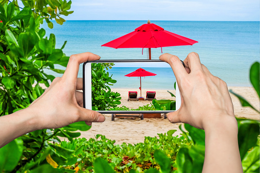 Woman Taking pictures on mobile smart phone show Red Umbrella on the beach