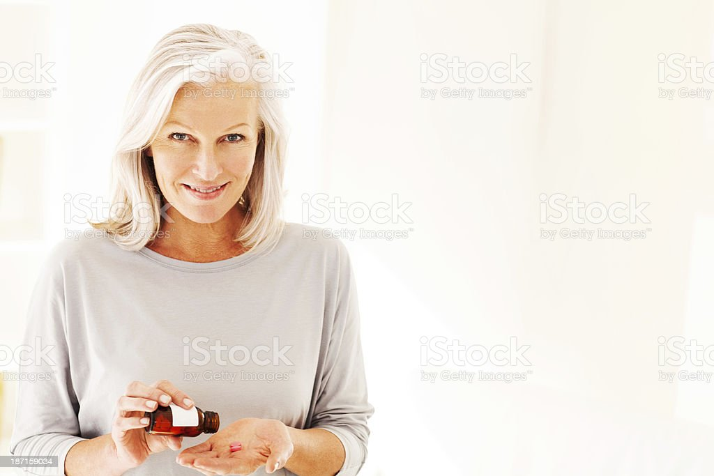 Woman Taking Pills From Bottle stock photo