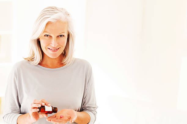 Woman Taking Pills From Bottle Portrait of happy senior woman taking pills from prescription bottle on to her hand. Horizontal shot. woman taking pills stock pictures, royalty-free photos & images