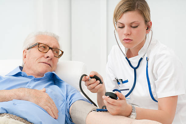 woman taking pressure levels of senior man - female nurse stock photos and pictures