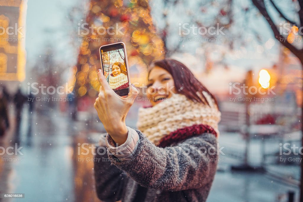 Woman taking selfie in front of the christmas tree - Photo
