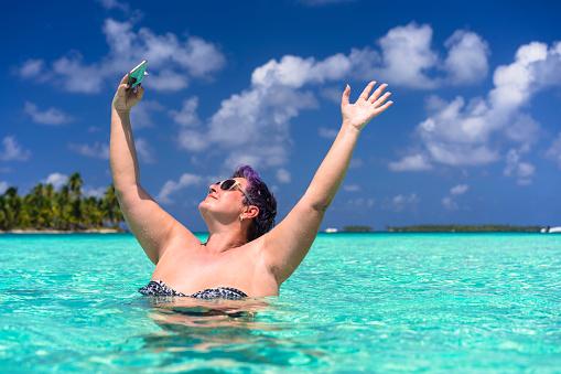 Woman taking selfie in turquoise sea near Isla de  Perro island in Caribbean See