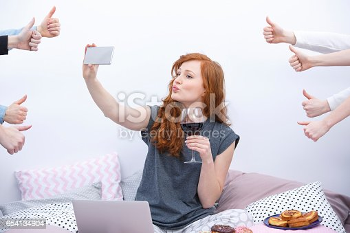 istock Woman taking selfie on bed 654134904
