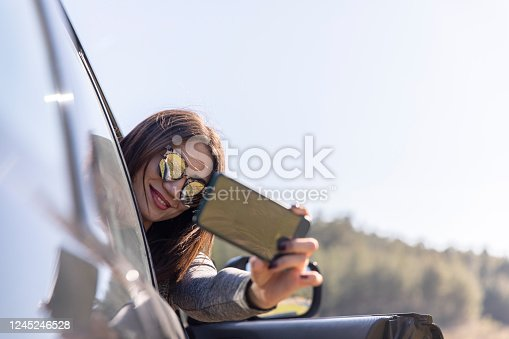 istock Woman taking selfie photo and inform something from smartphone while stting in car on roadtrip 1245246528
