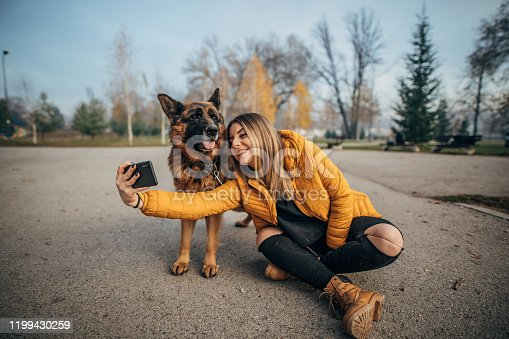 636418612 istock photo Woman taking selfie with dog in the park 1199430259