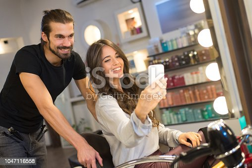 Beautiful smiling woman taking selfie with her favourite hairdresser.