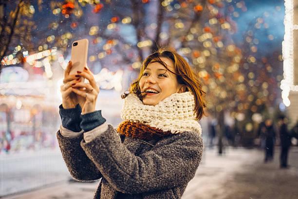 woman taking selfies on the christmas decorated street - weihnachtsstadt stock-fotos und bilder