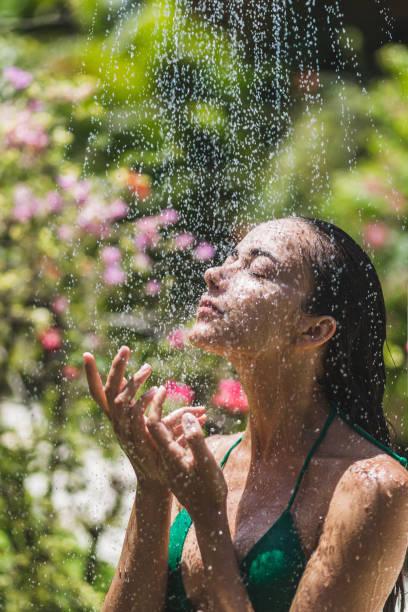 frau unter dusche draußen im grünen tropischen bali garten mit viel blumen. frische farbtupfer mit sauberem wasser. luxus-spa - sonnendusche stock-fotos und bilder