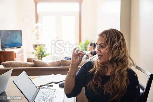 Woman taking temperature working from home on dinner table in small city apartment self-isolating from Covid-19. Teenage boys on the background. Mother and boys are latin american. Horizontal waist up indoors shot with copy space.