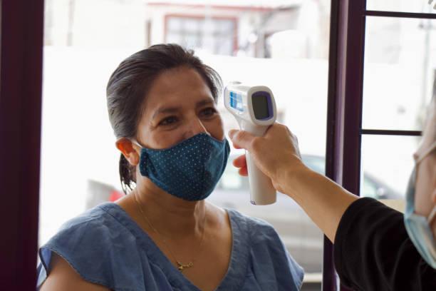 kvinna tar kroppstemperaturen - mature woman fever on white bildbanksfoton och bilder