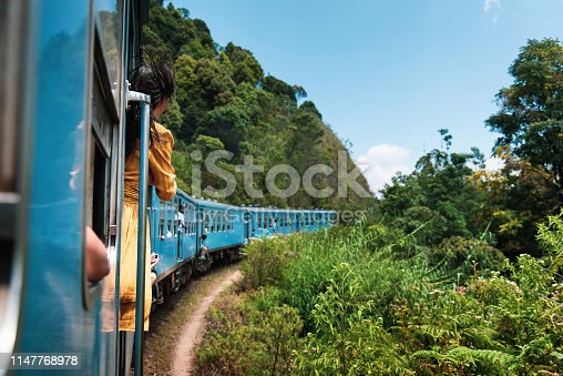 Woman taking the train ride through Sri Lanka tea plantations