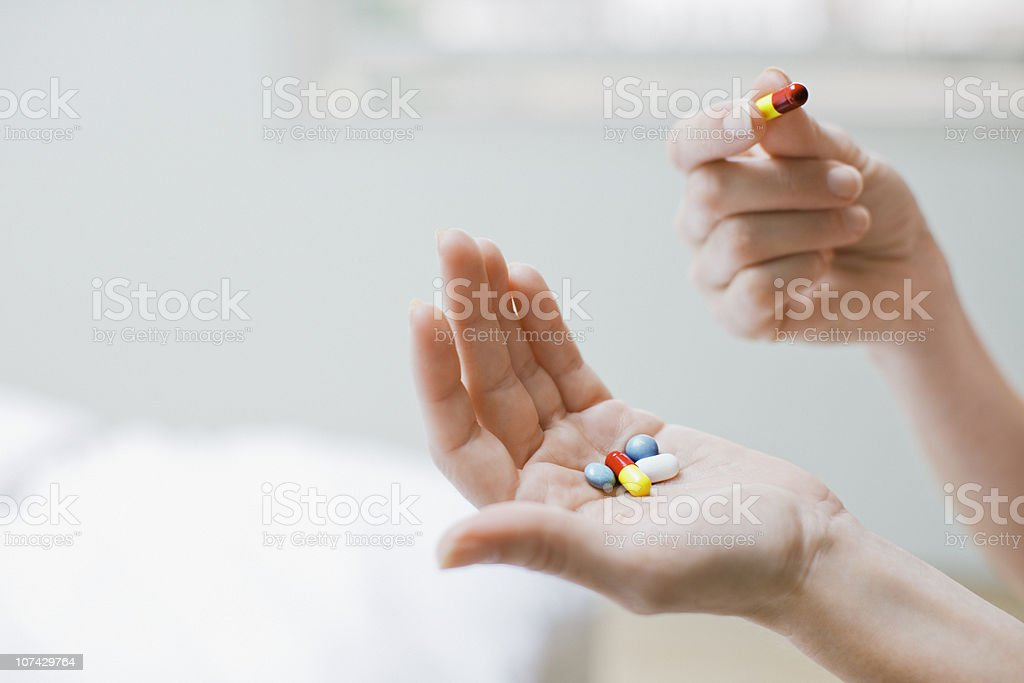 Woman taking vitamins and supplements stock photo