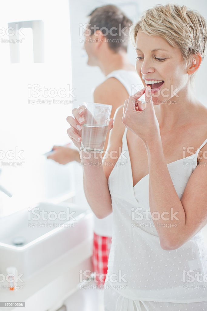 Woman taking vitamins in the morning stock photo