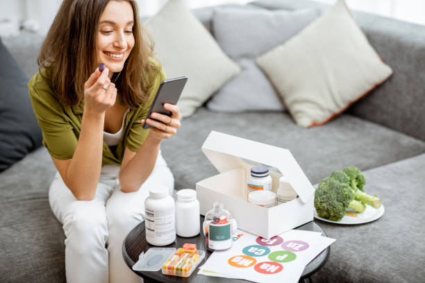 Woman taking vitamins or nutritional supplements Woman taking nutritional supplements in the form of pills while sitting with smart phone at home. Concept of individual online selection of food supplements. Preventive medicine biohacking stock pictures, royalty-free photos & images