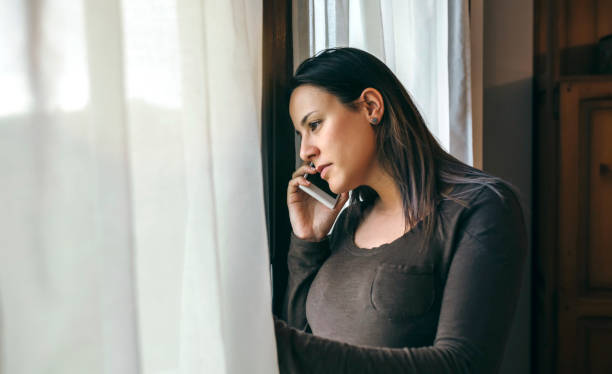 Woman talking cellphone and looking window Woman talking on cellphone and looking out the window taken on mobile device stock pictures, royalty-free photos & images