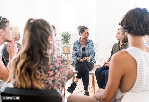 istock Woman talking in group therapy session 923258848