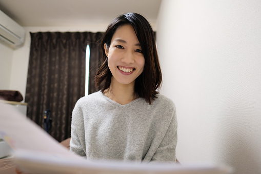 Young Asian woman talking in video call from house