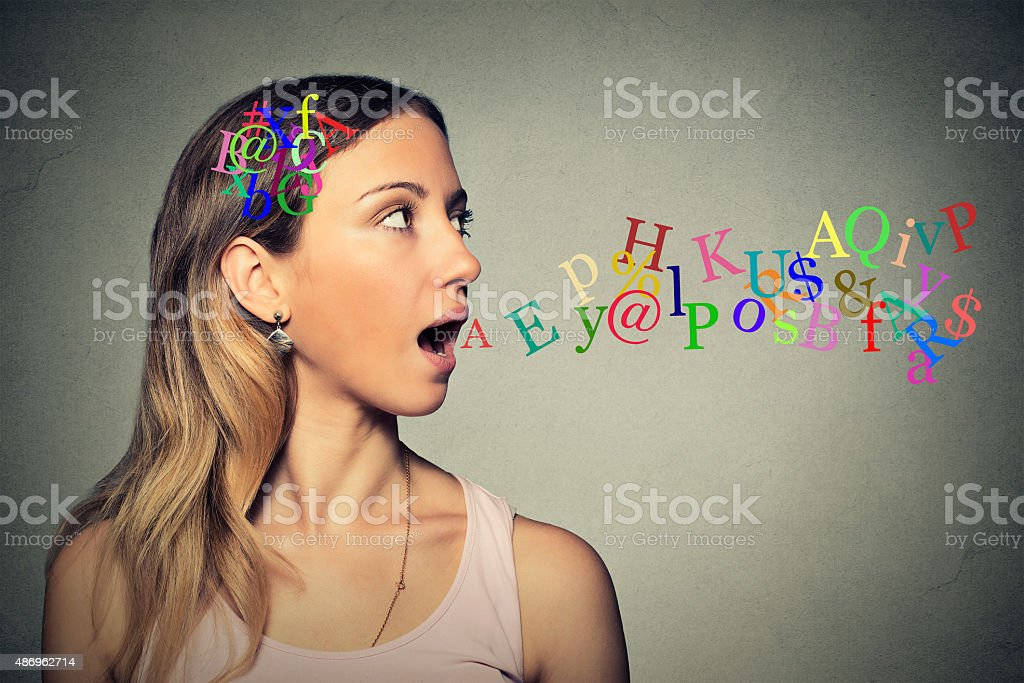 woman talking letters in head coming out of open mouth stock photo