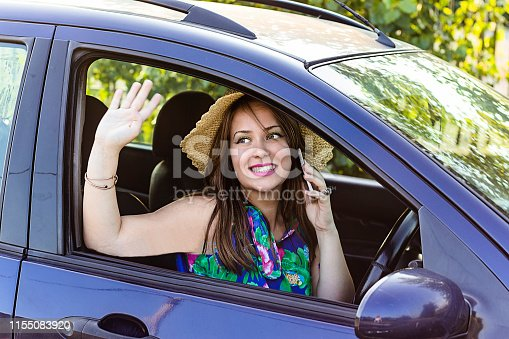 Young Woman in the Car Talks on the Smart Phone