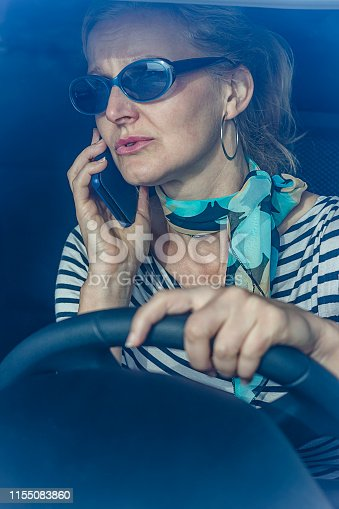 Cheerful Mature Woman in Business Suit Sitting of Her Car and Talking on Mobile Phone. Senior Businesswoman Using Phone While Traveling By a Car.