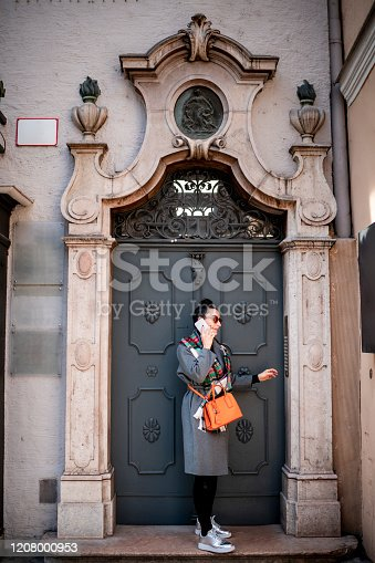 A female using a smart phone while getting buzzed on intercom at the front of old-style doors.