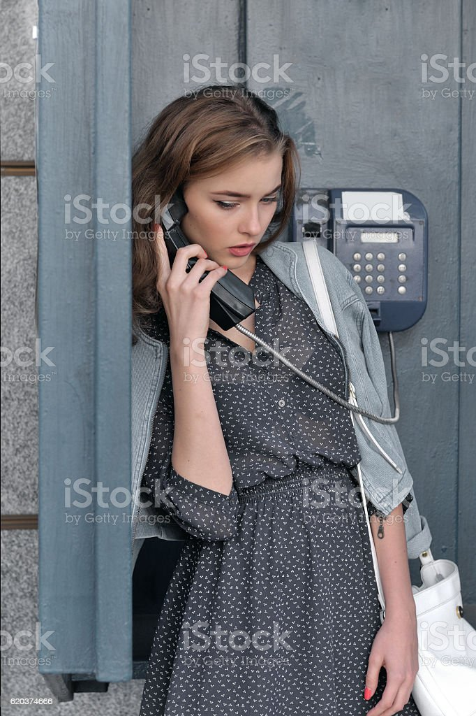 Woman talking on a pay phone on the street zbiór zdjęć royalty-free