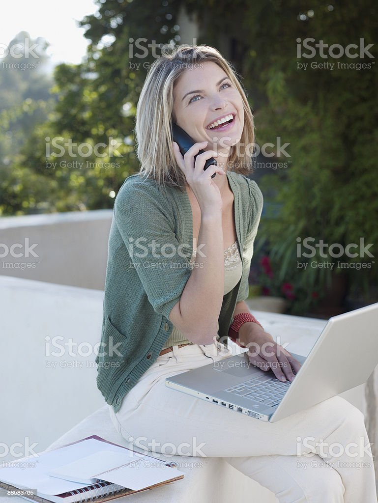 Woman talking on cell phone on patio royalty-free stock photo