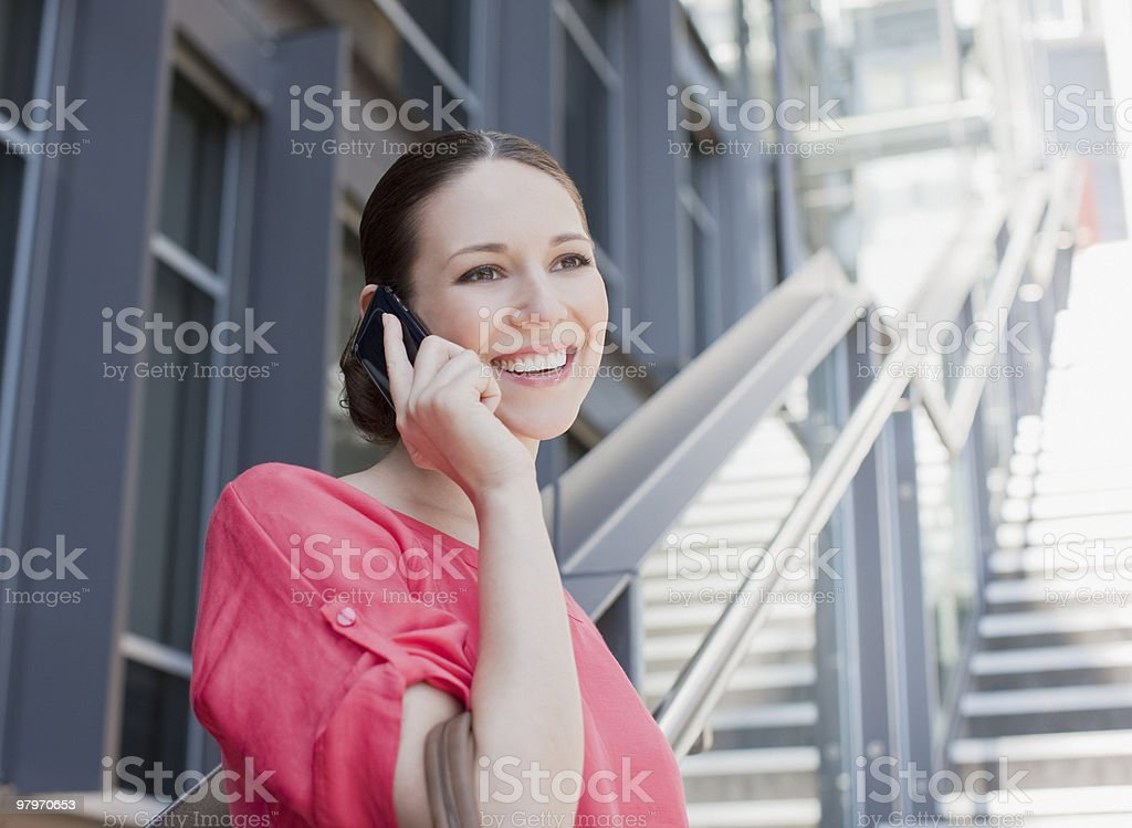 Woman talking on cell phone on sunny stairs royalty-free stock photo