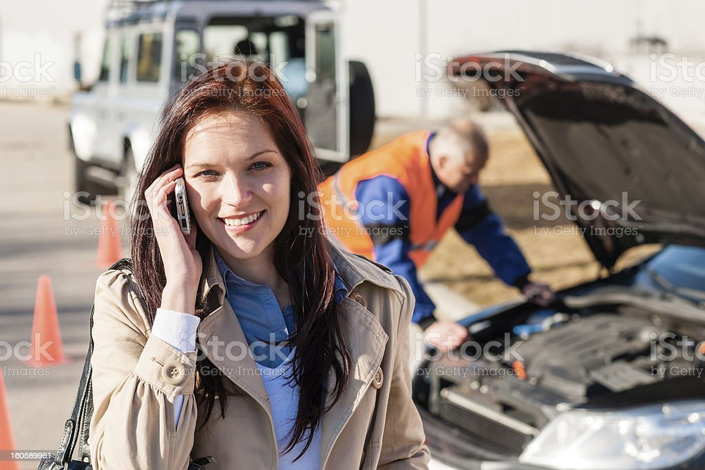 Woman talking on cellphone after car breakdown stock photo