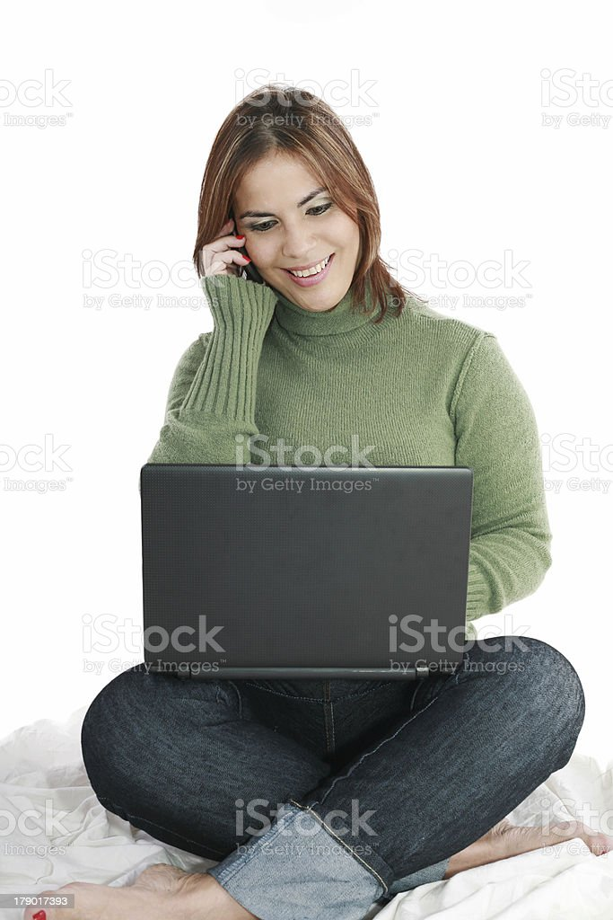 woman talking on mobile phone in front of laptop royalty-free stock photo