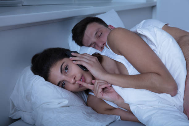 Woman Talking On Mobile Phone Privately Young Woman Talking On Mobile Phone While Her Husband Sleeps On Bed dishonesty stock pictures, royalty-free photos & images