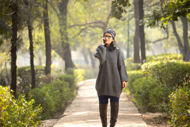 Woman talking on mobile phone while walking at park stock photo