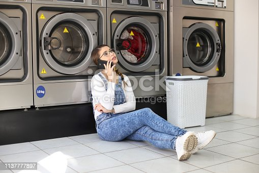 istock Woman talking on phone at a laundromat 1137777897