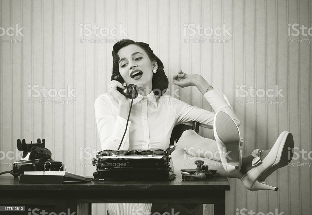 Woman talking on phone at desk Business woman puts her feet up on her desk on the phone 1950-1959 Stock Photo