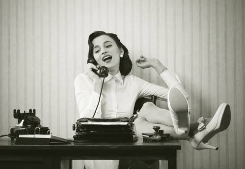 Woman Talking On Phone At Desk Stock Photo - Download Image Now