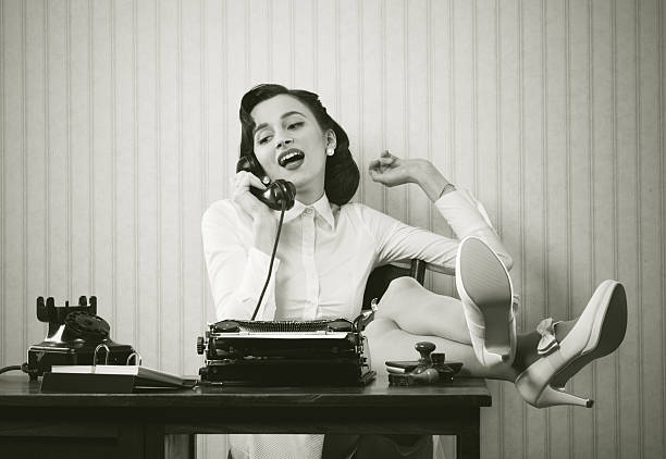 woman talking on phone at desk - vintage stock photos and pictures
