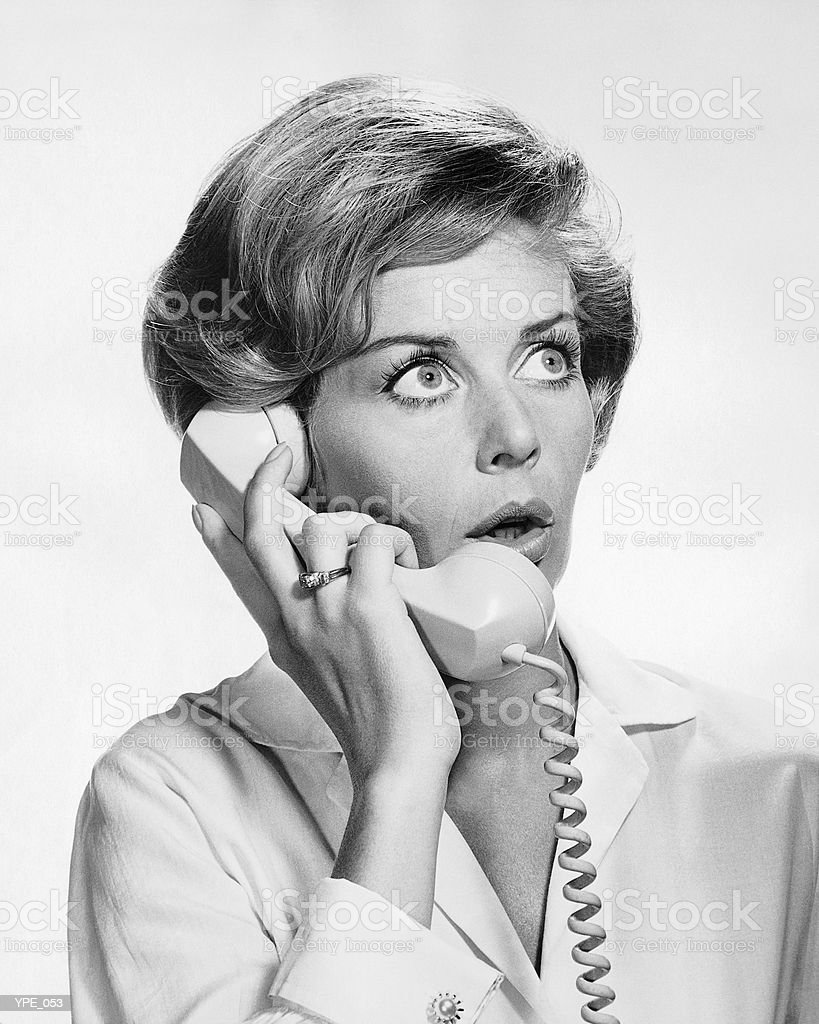 Woman talking on phone, looking surprised royalty-free stock photo