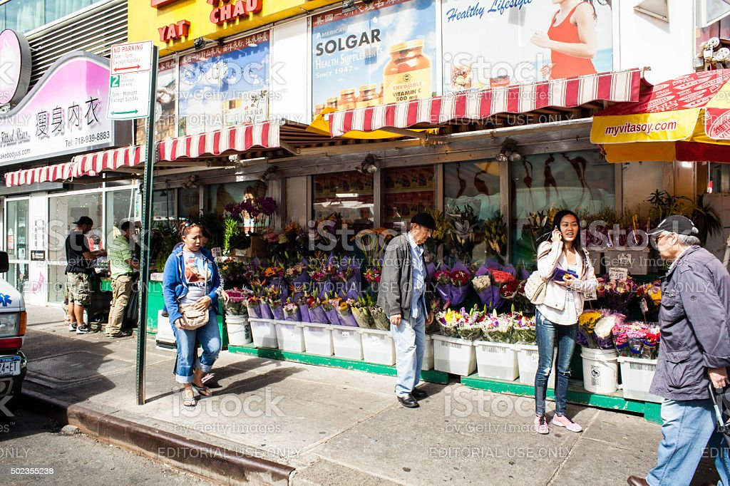 Woman Talking on Phone outside Chinatown Flower shop stock photo