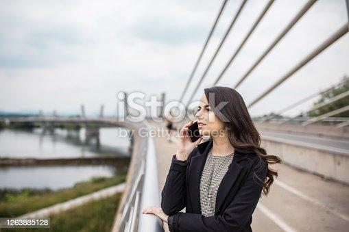 Woman talking on phone on bridge