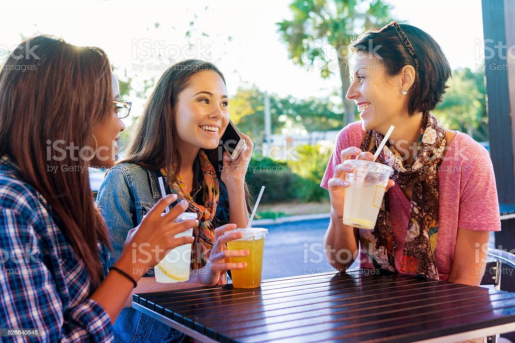 Woman talking on phone while having drinks with friends stock photo